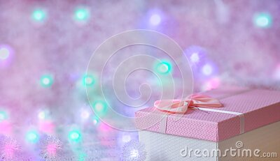 A gift box of soft pink color on a defocused background with burning lights of a garland. Festive, Christmas background. Free