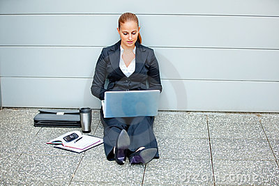 Pensive modern business woman using laptop