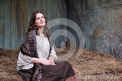 Portrait of an old-fashioned young woman sitting on a hay