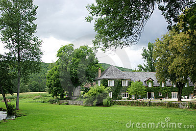 House in country garden behind trees