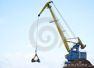 Yellow crane in cargo port translating coal. Industrial scene