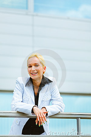 Business woman leaning on railing at office