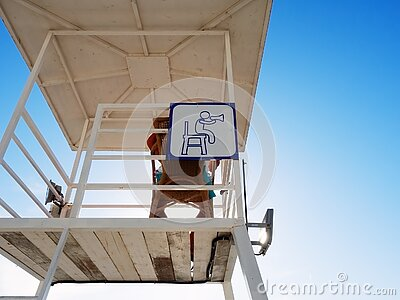 A white rescue tower with a lifeguard sitting in it and a white-blue sign attached to it