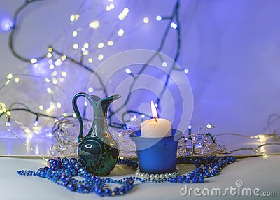Blue composition with candle and miniature mug, blue pearl ornaments in the foreground, white and blue light chain background,