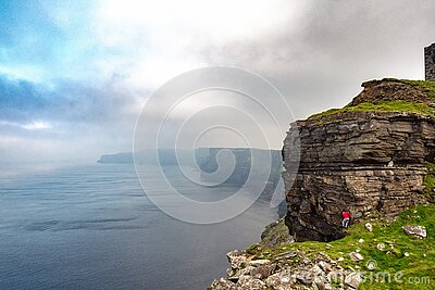 Male tourist in red shirt is climbing stone cliff, Epic view of rock structure of Cliff of Moher in the background, county Clare,
