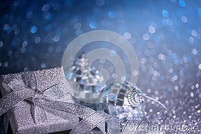 Blue festive Christmas background with defocused lights, gift box and shiny balls.