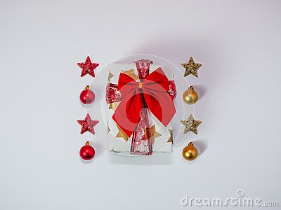 Creative Christmas composition made of gift box with red ribbon and baubles, christmas decorations, gold and red, flat lay, top vi