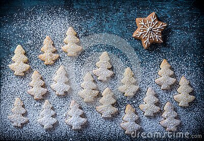 Snowy landscape with small Christmas trees and gingerbread star in sky