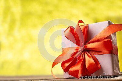 Christmas decoration on abstract  bokeh background. Merry christmas and Happy New Year Card. Gift box with red ribbon. Copy space