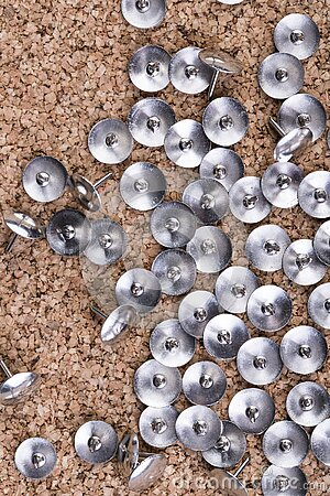 Scattered silver thumb tacks concentrated on the right side of a cork board