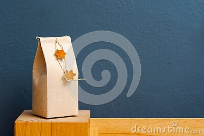 Gift box out of old beverage carton decorated with star shaped cut out dried roange peel standing on bedhead