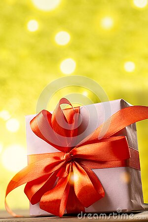 Christmas decoration on abstract bokeh background. Merry christmas and Happy New Year Card. Gift box with red ribbon. Copy space.