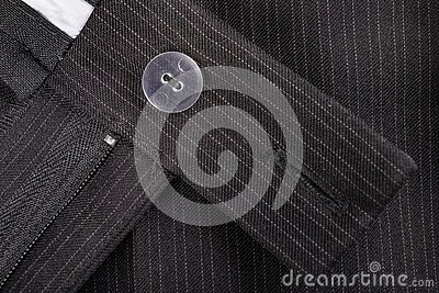 Zipper and button on men's trousers made of dark material. The fly in the pants