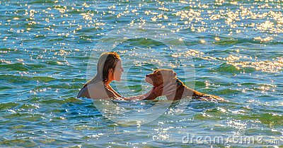 Woman and dog swimming and playing