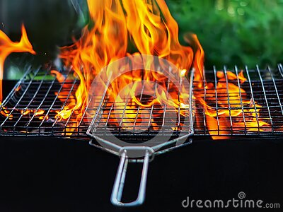 Fire in the grill. The red flames of a campfire make their way through the grill grate Firewood is burning in the backyard barbecu