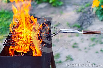 Fire in the grill. The red flames of a campfire blaze through the empty grill grate, burning wood in the backyard grill on the gre