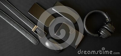 A black belt with golden buckle  leather-bound notebook  smartphone  headphones  computer mouse and case for glasses lie on a dark