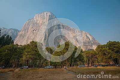 El Capitan seen from Yosemite valley floor. Cars and tourists on side of the road.