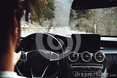 Portrait of adult driving a modern car on forest road during winter drive