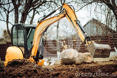 Landscaping works with mini excavator at home construction site. Terrain works