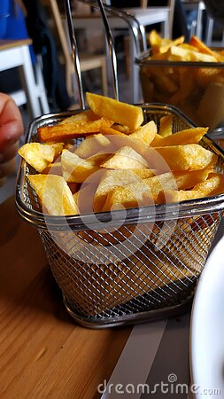Metal basket of fried potatoes on a restaurant table. The Belgians and the French contended for their authorship