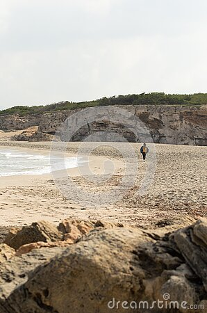 image of the shore of a beach with a girl walking in the distance.