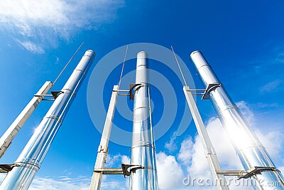 Exterior three metal ecological chimney pipe on top of a roof and sky as background.
