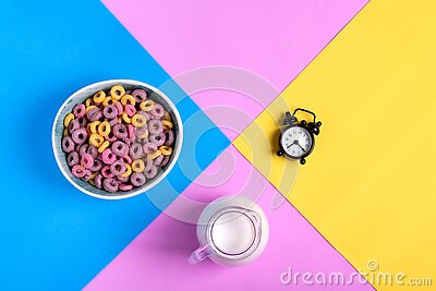 Multicolored fruit loops, jug of milk and alarm clock against the geometric background