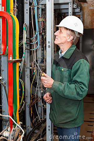 Electrician working in hard hat with cables