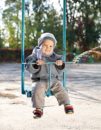 Baby boy playing on swing in autumn park