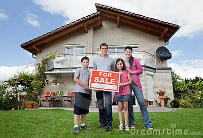 Family selling their home holding for sale sign