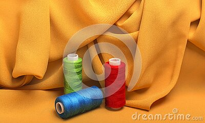 Background, texture, pattern wavy silk fabric and sewing thread on spools