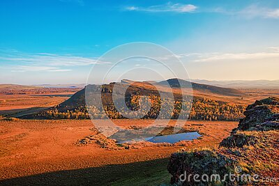 View of the steppe mountains and the lake from the cliff during sunset