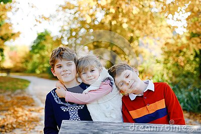 Portrait of three siblings children. Two kids brothers boys and little cute toddler sister girl having fun together in