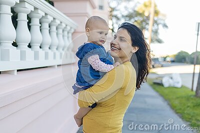 Beautiful happy mother holding her cute baby in peaceful neighborhood