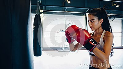 Young Asia lady kickboxing exercise workout punching bag tough female fighter practice boxing in gym fitness class. Sportswoman
