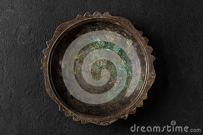 Empty vintage metal copper plate or bowl with blue rust on black stone background. low key. top view