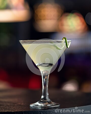 Alcoholic drink. Martini glass with lime decor on dark background, abstract blurred image. Copy space