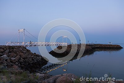 Small pedestrian bridge and jetty seen on the St. Lawrence river during a summer blue hour evening