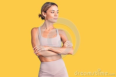 Beautiful caucasian woman wearing sportswear looking to the side with arms crossed convinced and confident
