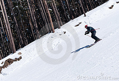 Skier carving down from steep slope