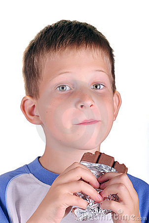 Young boy eating bar of chocolate