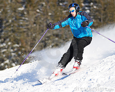Carving skier in powder snow with spray