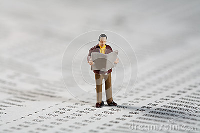 Private investor reads the financials in the paper