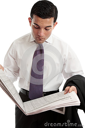 Businessman reads share prices in newspaper