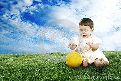 Sweet little child playing with a ball on the lawn