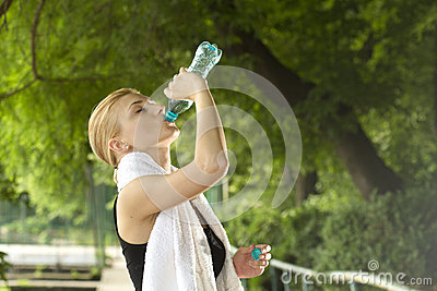 Sporty woman drinking water