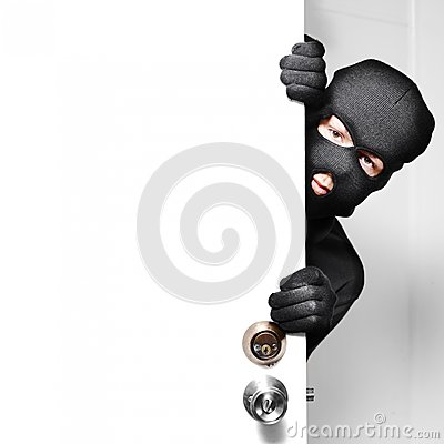 Home burglar opening house door with copyspace