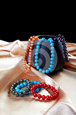 Bracelets and beads on a golden fabric