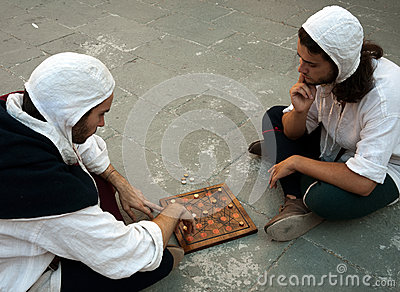 Two men in costume playing Mediaeval board game